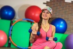 La muchacha blanca hermosa joven en un traje rosado de los deportes hace ejercicios físicos con pesas de gimnasia en el centro de Imagenes de archivo