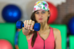 La muchacha blanca hermosa joven en un traje rosado de los deportes hace ejercicios físicos con pesas de gimnasia en el centro de Imagen de archivo