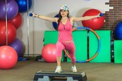 La muchacha blanca hermosa joven en un traje rosado de los deportes hace ejercicios físicos con pesas de gimnasia en el centro de Fotos de archivo libres de regalías