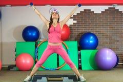 La muchacha blanca hermosa joven en un traje rosado de los deportes hace ejercicios físicos con pesas de gimnasia en el centro de Foto de archivo