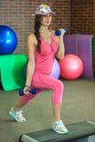La muchacha blanca hermosa joven en un traje rosado de los deportes hace ejercicios físicos con pesas de gimnasia en el centro de Fotografía de archivo