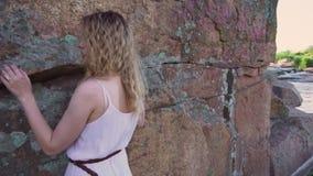 La muchacha bonita atractiva está haciendo girar cerca de una pared de piedra sobre un río transparente con la hierba verde, seño almacen de metraje de vídeo
