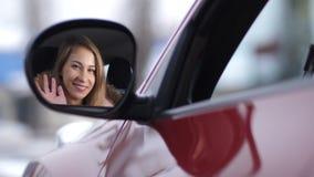 La muchacha bonita baja la ventana en el coche, miradas en el espejo lateral, ondas su mano y sonríe 4K MES lento almacen de video