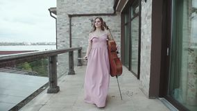 La muchacha bonita camina en balcón y jugar en el violoncelo almacen de video