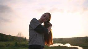 La muchacha bonita cepilla el pelo rojo largo en la naturaleza en la puesta del sol en la cámara lenta metrajes