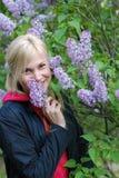 La muchacha bonita cerca de un arbusto de una lila fotografía de archivo libre de regalías