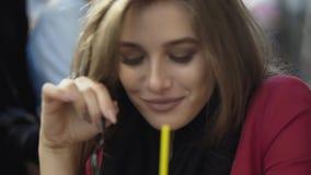 La muchacha bonita come espuma sabrosa en un café y sonrisas de la calle en la cámara almacen de video