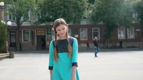 La muchacha bonita con dos coletas camina en la cámara en el área de la ciudad almacen de video