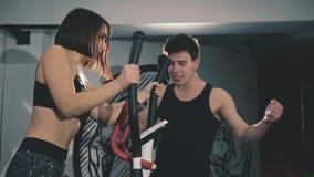 La muchacha bonita con el instructor ejercita en de pasos en el gimnasio en 4K almacen de metraje de vídeo