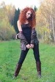 La muchacha bonita con el pelo rizado rojo se coloca entre árboles Imágenes de archivo libres de regalías