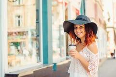 La muchacha bonita con el pelo rojo en un sombrero negro está bebiendo se lleva el café Día de verano asoleado Estilo de la ciuda Imagen de archivo