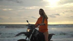 La muchacha bonita con el pelo rubio largo mira seriamente adelante, sentándose en una motocicleta, una sudadera con capucha anar metrajes