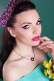 La muchacha bonita con las flores púrpuras enrruella en pelo Fotografía de archivo libre de regalías