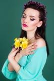 La muchacha bonita con las flores púrpuras enrruella en pelo Imágenes de archivo libres de regalías