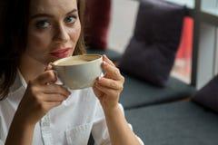 La muchacha bonita con una cara granujienta goza de un café fragante que se sienta en café Mujer de negocios que descansa durante Fotografía de archivo libre de regalías