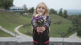 La muchacha bonita da el ramo de flores a la cámara metrajes