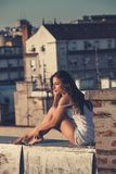 La muchacha bonita de la ciudad goza en puesta del sol en el tiro lleno summ del cuerpo del tejado imágenes de archivo libres de regalías