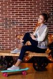 La muchacha bonita de la moda está sosteniendo el monopatín azul Foto de archivo libre de regalías