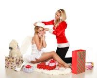 La muchacha bonita de la Navidad dos intenta encendido un sombrero de Santa Fotografía de archivo
