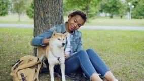 La muchacha bonita de la raza mixta está acariciando el perro lindo del inu del shiba y está hablando con él con la dulzura que d almacen de video