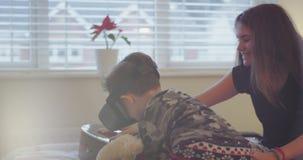 La muchacha bonita del adolescente puso a su hermano los vidrios de una realidad virtual por primera vez, niño pequeño muy se imp almacen de video
