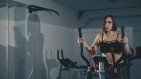 La muchacha bonita ejercita en de pasos en el gimnasio en 4K almacen de metraje de vídeo