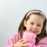 La muchacha bonita en color de rosa abraza su oso de peluche Fotos de archivo libres de regalías