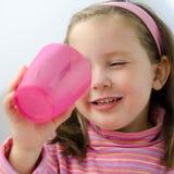 La muchacha bonita en color de rosa acaba su leche Fotos de archivo