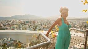 La muchacha bonita en guirnalda baila en las escaleras contra ciudad metrajes