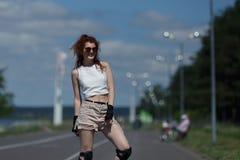 La muchacha bonita en pantalones cortos y tops patina en pcteres de ruedas en el camino en día soleado caliente Foto de archivo libre de regalías