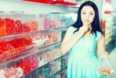 La muchacha bonita en tienda de los dulces coge los caramelos en bolso Fotografía de archivo