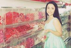 La muchacha bonita en tienda de los dulces coge los caramelos en bolso Fotografía de archivo libre de regalías