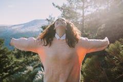 La muchacha bonita en un suéter coloreado coralino se separa los brazos con una cara feliz imagen de archivo