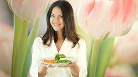 La muchacha bonita en un traje del blanco sostiene una placa grande de verduras hervidas y la empuja adelante Guiños morenos Sano almacen de metraje de vídeo