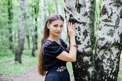 La muchacha bonita en vestido ruso negro con bordado se inclinó contra abedul Fotografía de archivo libre de regalías