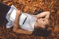 La muchacha bonita es relajante con la tableta digital al aire libre Fotos de archivo libres de regalías