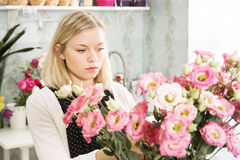 La muchacha bonita está eligiendo las flores para sí misma Fotografía de archivo