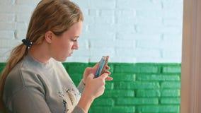 La muchacha bonita está haciendo el selfie del espejo con el teléfono elegante mientras que se coloca en sitio apropiado en tiend metrajes