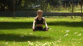 La muchacha bonita está haciendo yoga en parque almacen de metraje de vídeo