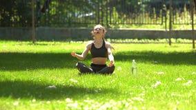 La muchacha bonita está haciendo yoga en parque almacen de video