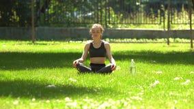 La muchacha bonita está haciendo yoga en parque metrajes