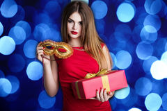 La muchacha bonita está llevando a cabo la caja y la máscara rojas de regalo Imágenes de archivo libres de regalías