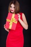 La muchacha bonita está llevando el vestido de la moda con la caja de regalo Imagenes de archivo