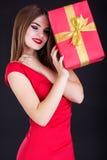 La muchacha bonita está llevando el vestido rojo con la caja de regalo Foto de archivo