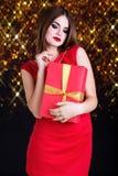 La muchacha bonita está llevando el vestido rojo con la caja de regalo Fotos de archivo libres de regalías