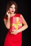 La muchacha bonita está llevando el vestido rojo de la moda con el regalo Foto de archivo libre de regalías