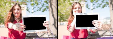 La muchacha bonita está ofreciendo algo en una tableta/un sistema Fotos de archivo libres de regalías