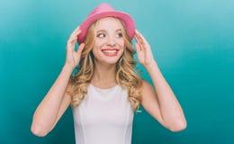La muchacha bonita está pareciendo derecha Ella es permanente y que sostiene sombrero rosado con ambas manos La muchacha es muy a Foto de archivo libre de regalías