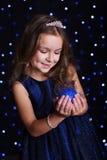 La muchacha bonita está sosteniendo la bola azul de la Navidad Imagen de archivo