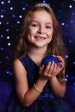 La muchacha bonita está sosteniendo la bola azul del árbol de navidad Fotografía de archivo